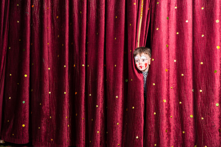 Fun little boy in makeup waiting for his acting cue poking his head out between the curtains as he waits to make his entrance on stage during the performance