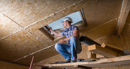 Low Angle View of Male Construction Worker Builder Crouching on Elevated Scaffolding near Ceiling and Inspecting Frame of Sky Light Window in Unfinished House with Exposed Particle Plywood Board