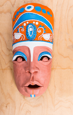 High Angle View of Handicrafted Clay Tribal Mask Sculpted Carefully and Painted Colorfully in Blue, Orange and White