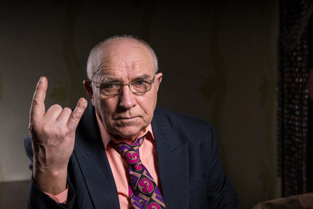 Elderly man making a horns gesture depicting heavy metal rock music or the sign of the devil, seated head and shoulders portrait on a dark background with copyspace