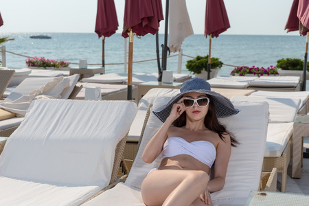 Young woman in a bikini relaxing alongside the ocean on a comfortable recliner chair at an upmarket resort enjoying her summer vacation