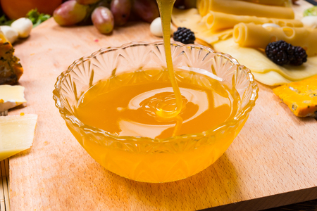 Pouring healthy golden honey into a round glass bowl on a table for use as a dip and spread