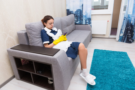 Work shy housekeeper or maid taking a break sitting on a comfortable sofa in her uniform and rubber gloves checking her mobile phone