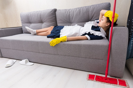 Exhausted housekeeper relaxing on the job lying on a couch in her uniform taking a nap with her mop alongside