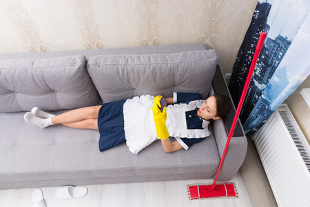 Lazy work shy housekeeper in uniform taking a break lying on her back on a sofa with her mop beside her checking her mobile phone, view from above