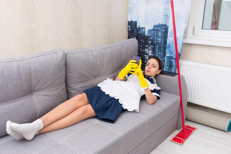 Lazy indolent maid or housekeeper in uniform lying relaxing on a comfortable sofa with her mop alongside checking her mobile phone