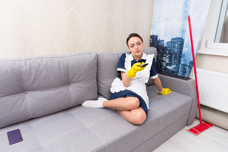 Lazy housekeeper or maid in uniform taking a break putting her feet up on the sofa as she selects a television program to watch