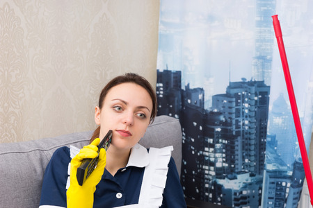 Thoughtful housekeeper in a high-rise apartment sitting in front of a window with a view of the sity rooftops with her mobile in her hand
