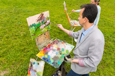 Couple of middle-aged fashionable professional artists working on a sketchbook painting a garden scene with flowers in a park