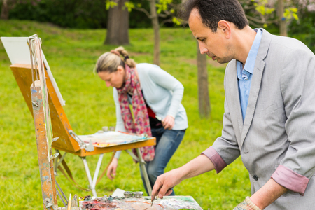 Two fashionable creative painters working  on a trestle and easel painting with oils and acrylics during an art class in a garden
