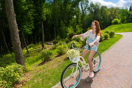 Young woman sitting on her bicycle with a bouquet of little white flowers in a basket in a park with background of different trees