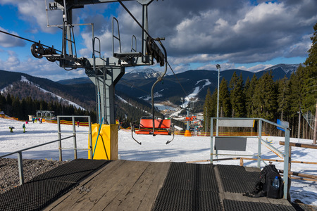 Station of ski lift with chairs against mountain view in a ski-resort on a sunny day in winter period