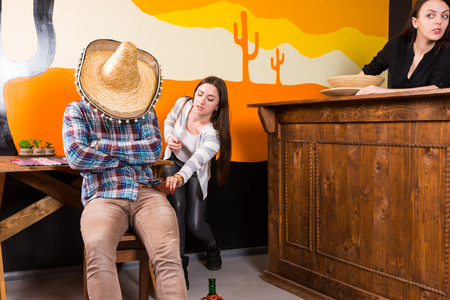 Girls want to steal a purse from a man who got drunk and fell asleep sitting on a chair and covered his face with a sombrero in a Mexican bar