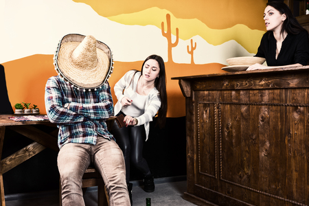 Females want to steal a purse from a man who got drunk and fell asleep sitting on a chair and covered his face with a sombrero in a Mexican bar