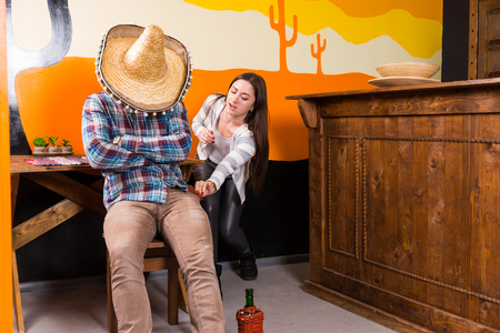 A girl wants to steal a purse from a man who got drunk and fell asleep sitting on a chair and covered his face with a sombrero in a Mexican bar