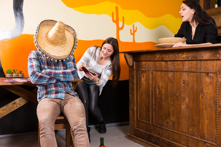 Females stealing a purse from a man who got drunk and fell asleep sitting on a chair and covered his face with a sombrero in a Mexican bar