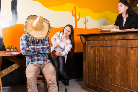 Young females want to steal a purse from a man who got drunk and fell asleep sitting on a chair and covered his face with a sombrero in a Mexican bar