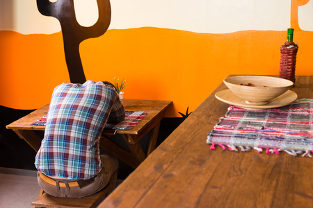 A man in a Mexican bar got drunk and fell asleep sitting on a chair