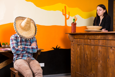 A man in a bar got drunk and fell asleep sitting on a chair and covered his face with a sombrero, female bartender looks at him disapprovingly