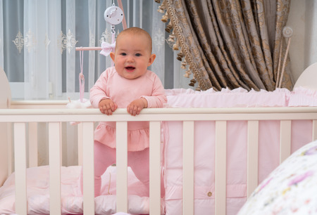 A happy, laughing baby standing in a crib in a pink bedroom scene.