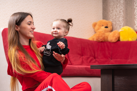 Beautiful young mother with long blonde hair sitting on a floor near red couch and holding her smiling little baby girl in her hands. Low angle portrait with copy space