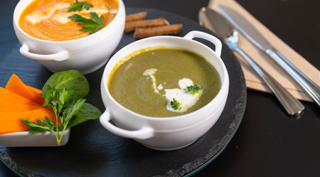 Photo for Bowl of tasty broccoli and spinach soup with a second bowl of butternut or pumpkin soup behind on a black circular wooden board for delicious appetizers to a dinner - Royalty Free Image
