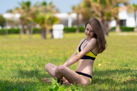 Foto de Pretty slender young woman in a yellow bikini sitting on the grass in a park in the shade of a tree smiling as she looks down - Imagen libre de derechos