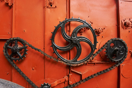 Photo pour high-quality metal gears and chains on an old tractor of bright orange color in the museum of agricultural equipment - image libre de droit