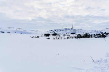 high metal towers for cellular and internet on a hill surrounded by snow in the tundra on a frosty winter day