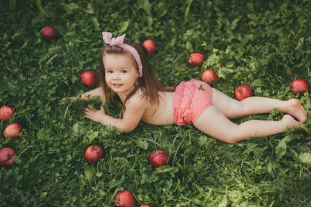 Photo pour A child with long hair lying on the grass with red apples. The girl is wearing pink panties and a bow. Sunny and warm. - image libre de droit