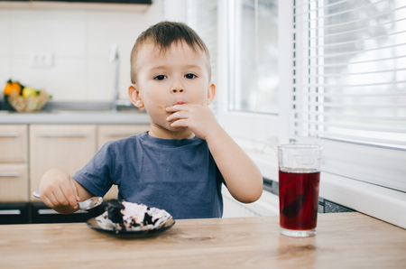 A small child eats black chocolate cake, at home in the kitchen next to the red juice of pomegranates