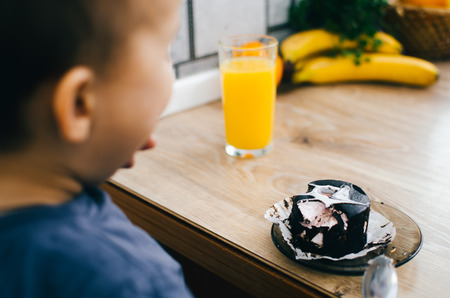 A small child eats a black chocolate cake, at home in the kitchen