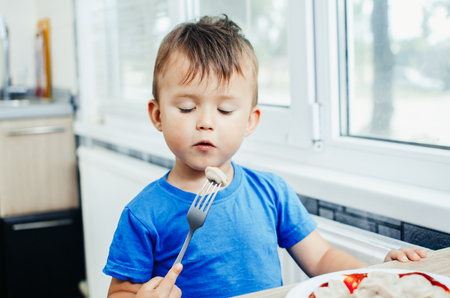 Hungry baby eating dumplings in the kitchen sitting on a chair in a blue t-shirt