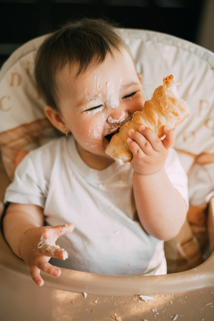 Photo for baby in the kitchen eagerly eating the delicious cream horns, filled with a vanilla cream - Royalty Free Image