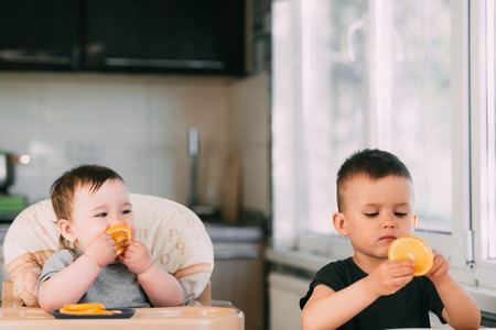 Children brother and sister eat in the kitchen orange cut into slices very fun and amicably