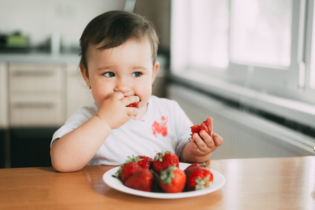 Little girl child in white t-shirt eating strawberries all smeared and dirty very funny