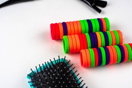 Colorful hair bands on a white background next to a comb coll