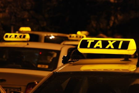 Illuminated taxi sign on roof of waiting cabs