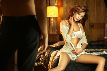 Photo pour Cute brunette in lingerine sitting on the bed and waiting for a man - image libre de droit