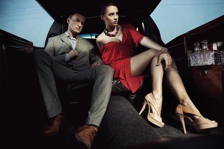 Photo pour Beautiful couple sitting in a limousine - image libre de droit