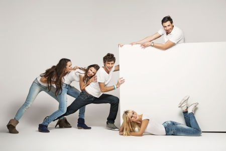 Photo pour Young people pushing empty board - image libre de droit