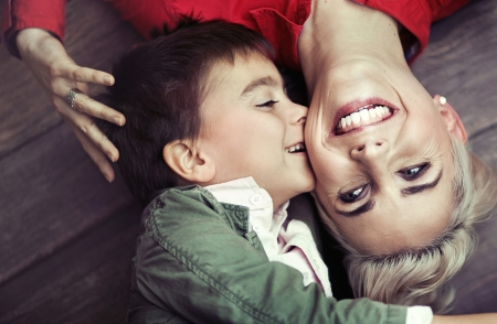 Young boy kissing his smiling mom