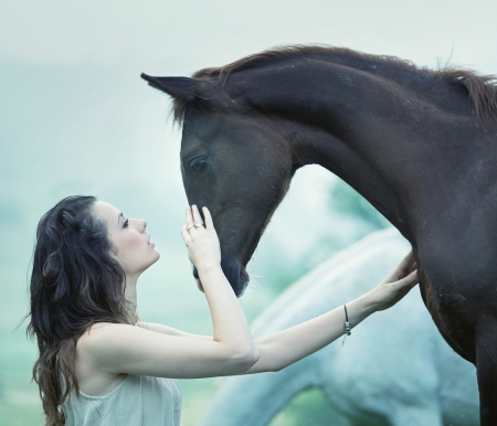 Sensual woman stroking a wild horse