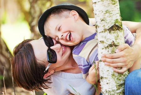 Laughing small boy hugged by his pretty mother