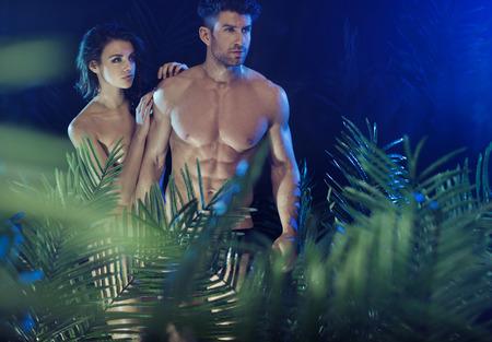 Sexy couple among the tropical green plants