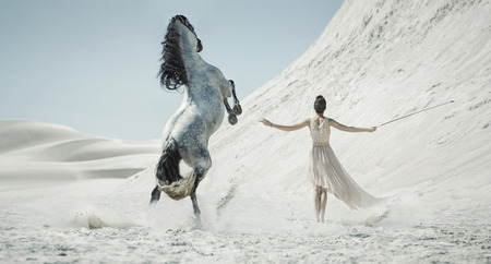 Pretty lady with white horse on the desert