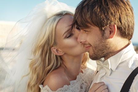 Photo pour Romantic photo of young bride kissing her husband - image libre de droit