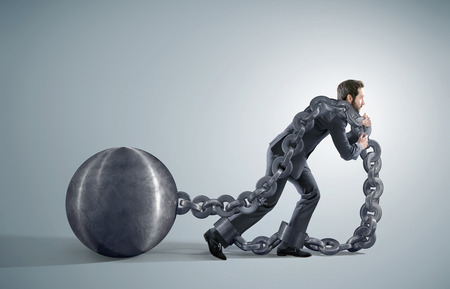 Exhausted businessman dragging heavy chains