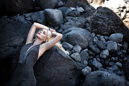 Foto per Adorable blond woman lying on the giant stones - Immagine Royalty Free