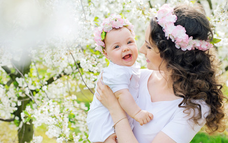 Photo for Young mom and her little baby relaxing in a spring orchard - Royalty Free Image